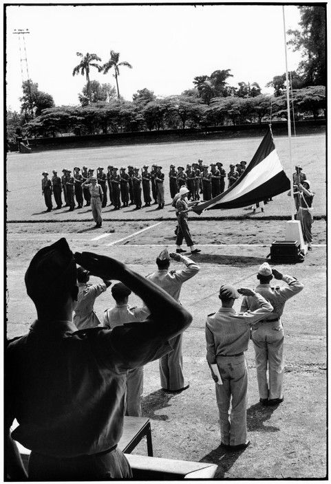 Henri Cartier-Bresson // Indonesia, 1949 -- Java. Dutch transfer. Dutch flag comes down and Republic flag goes up at ceremony in town stadium.
