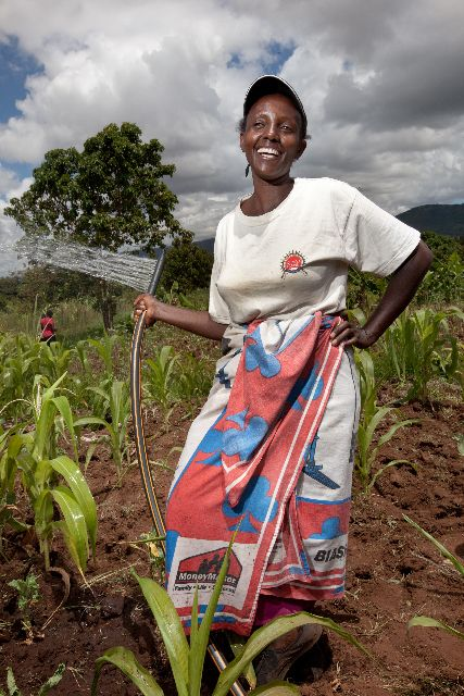 Penniah Wambah proudly demonstrates to neighbors how the Kickstart pumps can increase their farm's yield. (Photo credit: Esther Havens)