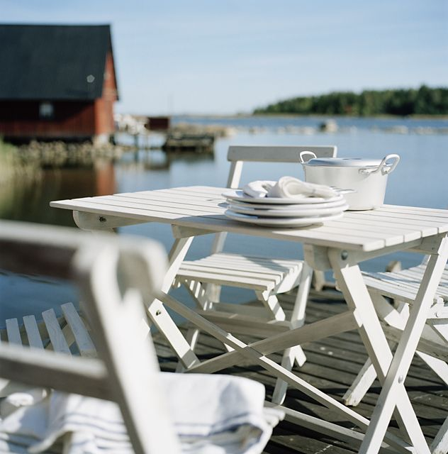 White garden furniture on a wooden jetty.