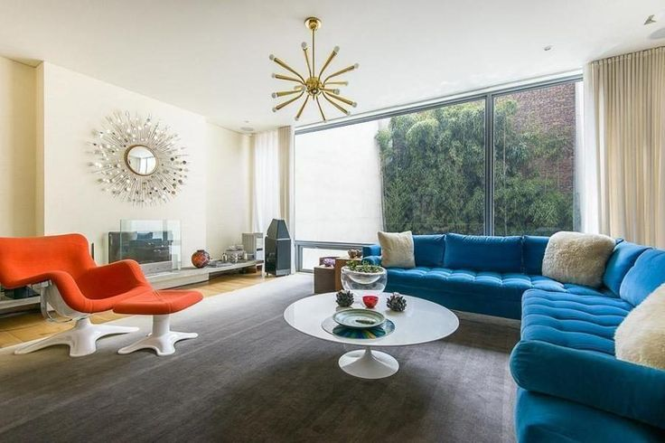 This NYC living room has wood floors, a gray area rug, blue tufted sectional couch, circular coffee table, orange lounge chair and metallic decor.