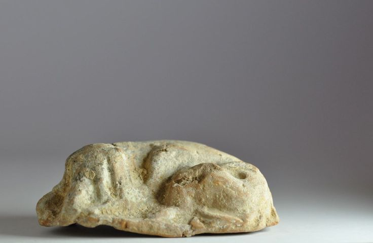 Greek terracotta statuette of sleeping dog, 4th-1st century B.C. Greek terracotta crouching dog, 9.8 cm long. Private collection