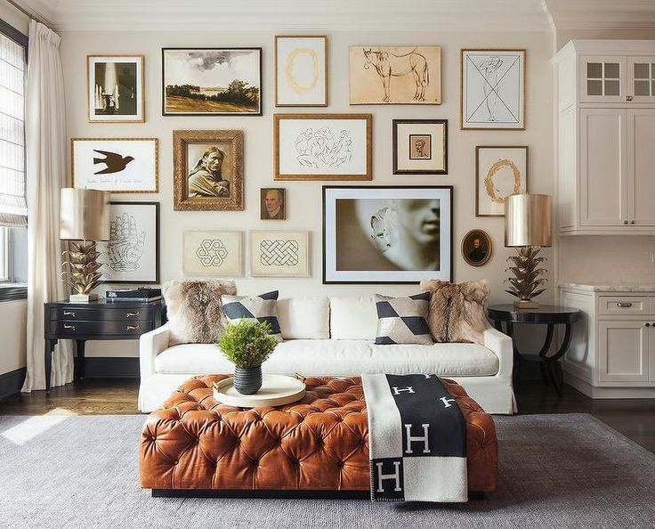 An Eclectic Art Gallery Stands Over A White Skirted Sofa Lined With Black  And Gray Pillows Flanked By Mismatched Black End Tables And Metal Artichoke  Lamps ...