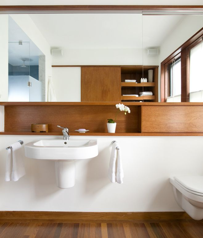 Wall-hung sinks are sleek, but leaves no room for storage, so architects Pamela Butz and Jeffery Klug installed a small shelf above it. The space to the right appears to be an extension of the shelf, but is actually a panel that conceals the water tank of the wall-hung toilet. Photo by: Eric Roth