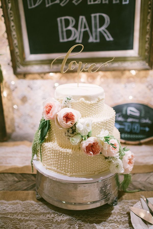 dotted boho wedding cake - photo by Vis Photography http://ruffledblog.com/handcrafted-boho-woodsy-wedding #weddingcake #cakes