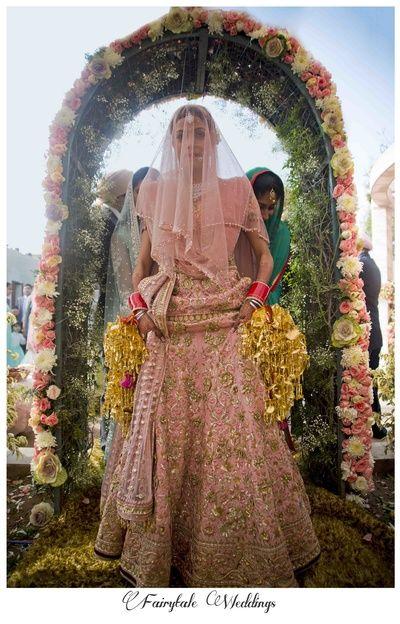 heavy bridal sharara , bridal lehenga in light pink, light pink bridal lehenga , sikh bridal lehenga , sikh bridal outfits , long top bridal lehenga , sheer veil , pastel bridal lehenga , morning wedding, bridal entrance , floral arch , pink and gold f