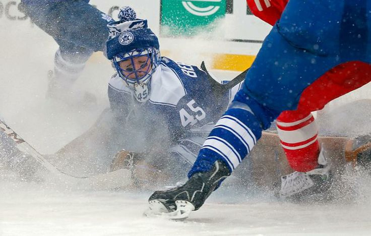 Maple Leafs goalie Jonathan Bernier gets an icy reception as he stops a shot on goal. (Paul Sancya/AP)