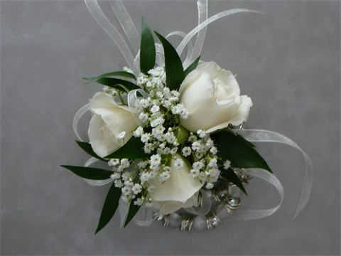 Simple bridesmaid wrist corsage with white roses and baby's breath.