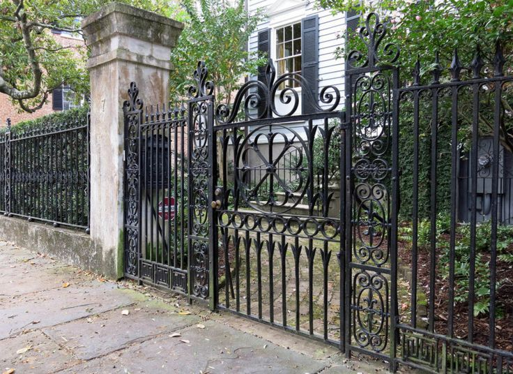 A Tall Intricate Wrought Iron Fence With An Ornate Gate With