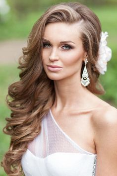 one side half up wavy wedding hairstyle with flower
