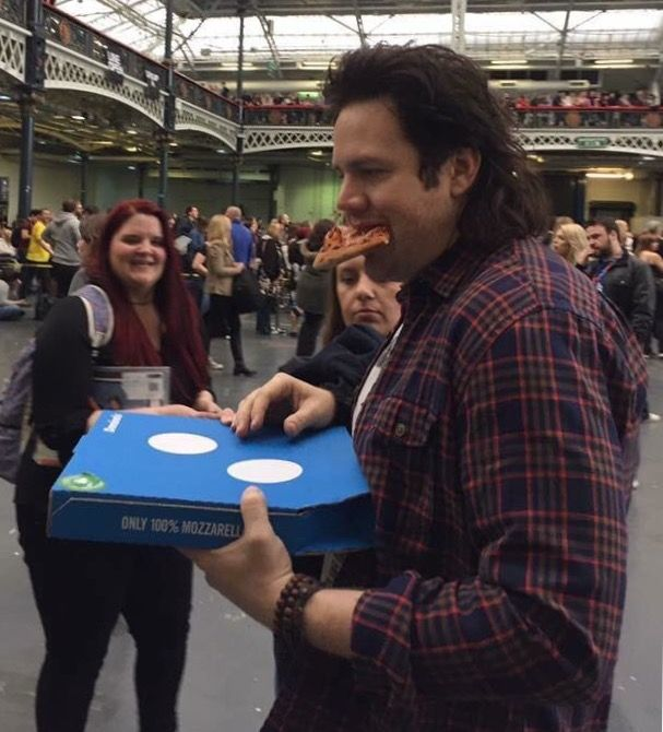 Josh McDermitt wishing he could eat that piece of pizza, but his hands are full with more pizza