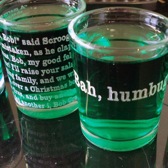 """Four Christma shot glasses, engraved with quotes by Scrooge from Charles Dickens The Christmas Carol.    The four quotes are:    """"I am as light"""