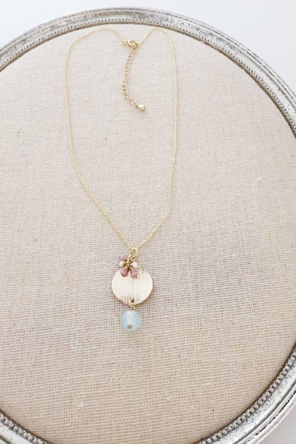コインのようなパーツを使ったネックレスです。 淡いブルーの天然石と、ピンク×ホワイトの小さな石がとっても可愛いですよ。タートルネックセーターや、シ...|ハンドメイド、手作り、手仕事品の通販・販売・購入ならCreema。