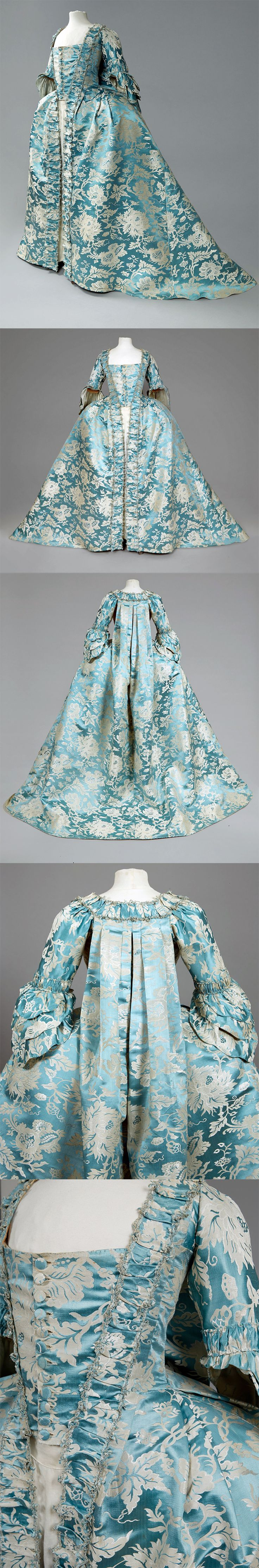 Robe a la Francaise, mid 18thC, Open gown of Chinese cerulean blue silk woven with a large-scale white and platinum floral, having elbow length sleeve with lobed triple cuff gathered into a ruched band, square neckline, bodice front panel with self buttons, trimmed with furbelows edged in silk fly braid, sacque back, pleated skirt side panels with pocket slits, back lacing bodice lining in various cottons, the front printed in a red windowpane. | Whitaker Auctions via SmugMug