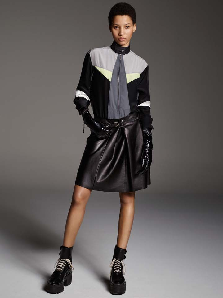 Look 4 of the Louis Vuitton 2016 Prefall Collection is a zipped color blocked blouse and leather skirt. Accessorized with extra long over the elbow black patent leather gloves and platform half-boots. Designed by Nicolas Ghesquière, photographed by Karim Sadli.