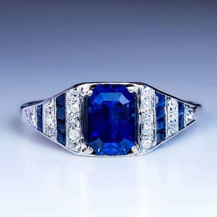 circa 1920 A platinum hand-crafted ring is centered with an emerald cut natural sapphire (8.2 x 5.85 x 4.4 mm, approximately 2.11 ct) of a beautiful cornfl