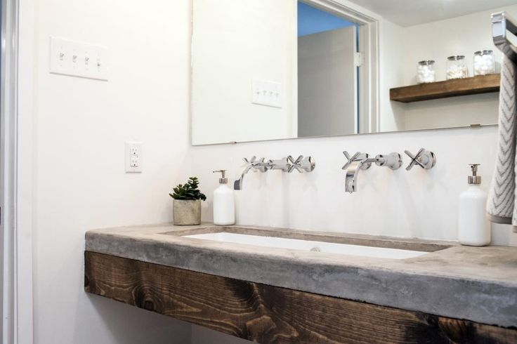 Poured concrete countertops and wood shelving add much-needed texture to the formerly stark bathroom. Dual faucets installed on the walls uphold the original midcentury vibe and save counter space, too. See more stunning photos from this makeover.
