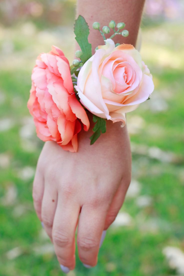 Whimsical and fun medium corsage to fit any coral or peach colored theme. This corsage features: - Coral Pink Ranunculus - Light Peach and Coral Semi-closed Rose - Light Green Bead Spray Felt and or r
