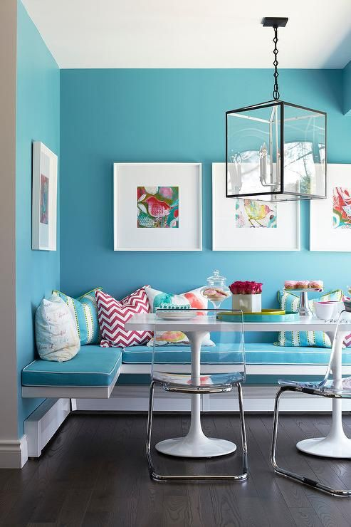 Colorful framed bird art is mounted to blue walls painted in Benjamin Moore Spa Day above an l-shaped white floating dining bench accented with blue seat cushion lined with white piping and topped with red and blue accent pillows.