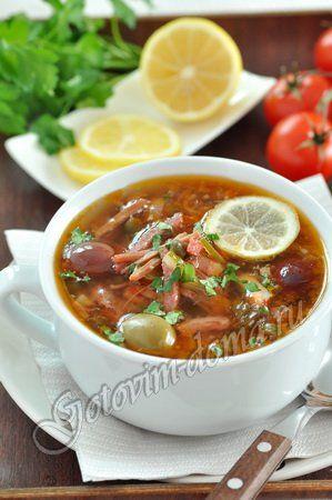 Солянка готовится на бульоне из говядины, копченой грудинки, сосисок. Все резать тонкой соломкой. Лук спассеровать + томат-пюре на 5 мин. В тарелку: очищенный от кожицы кусок лимона, маслину целиком, сметану.  В кипящий бульон положить: лук, огурцы, оливки, мясные продукты и варить 10 минут на медленном огне. Добавить лавровый лист, перец горошком, соль и еще варить 5 минут.