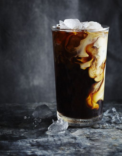 Glass of iced coffee with cream swirling