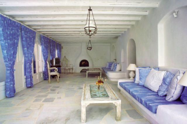 Το μακρόστενο σαλόνι με τις μπαλκονόπορτες και τα χτιστά καθιστικά με τα μπλε αποχρώσεων μαξιλάρια.