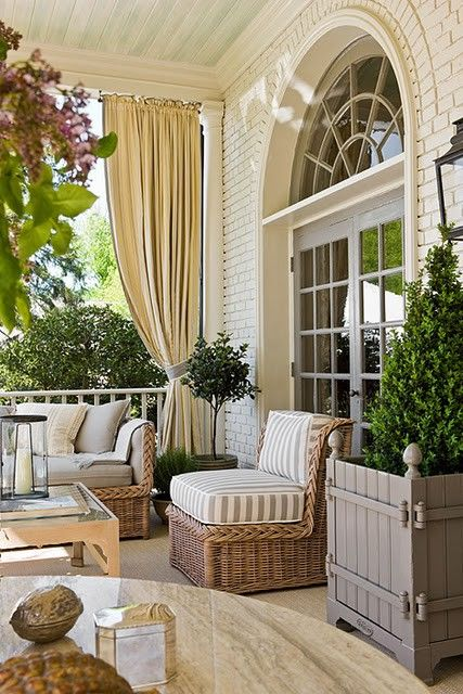 White painted brick, natural wicker furniture, grey planters, faded blue covered-porch ceiling... simply beautiful.