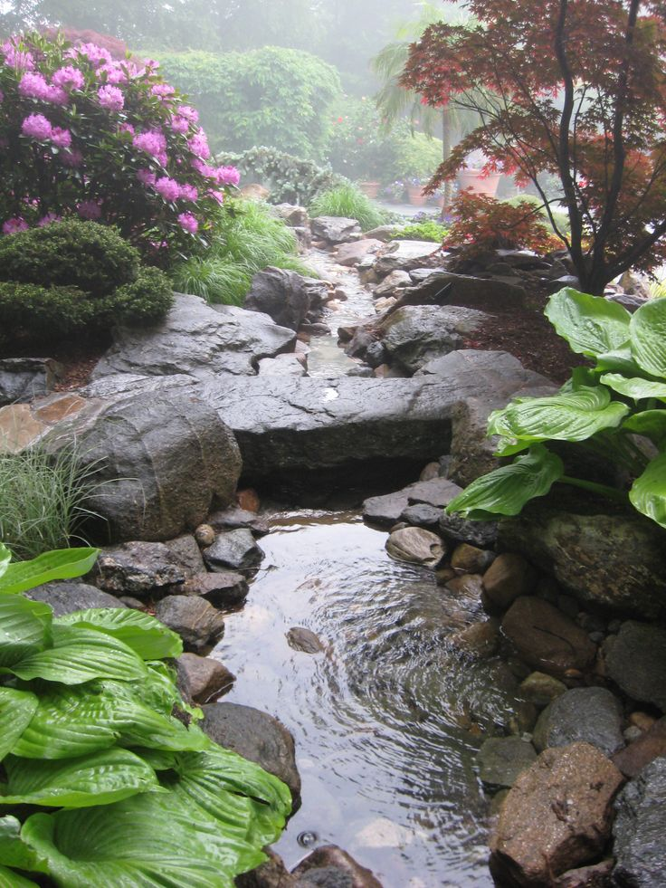 Backyard waterfalls, water garden stream with stone bridge in a Connecticut backyard by Matthew Giampietro.
