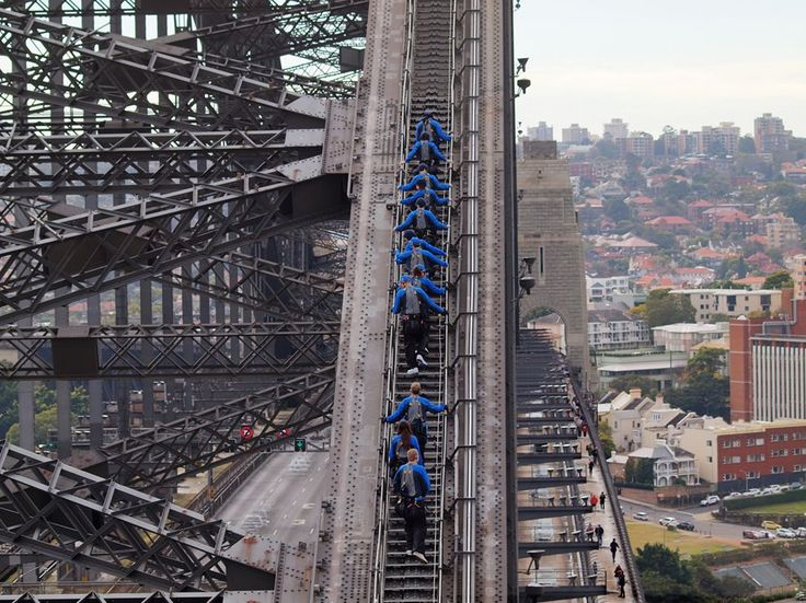 Sydney Harbour Bridge climbers don special suits for the 2.5-hour climb. The suits are meant to blend in with the bridge and are designed not to distract passing traffic below. The climb starts from the southern end. The north shore suburb Kirribilli can be seen to the right of the bridge.