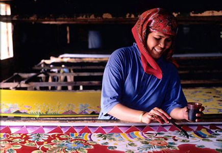 A Malaysian woman creates colorful batik fabric using the traditional process.