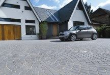 A large modern driveway featuring Brett Alpha 60mm Large 210x140mm block paving bricks which have been laid in a circular pattern