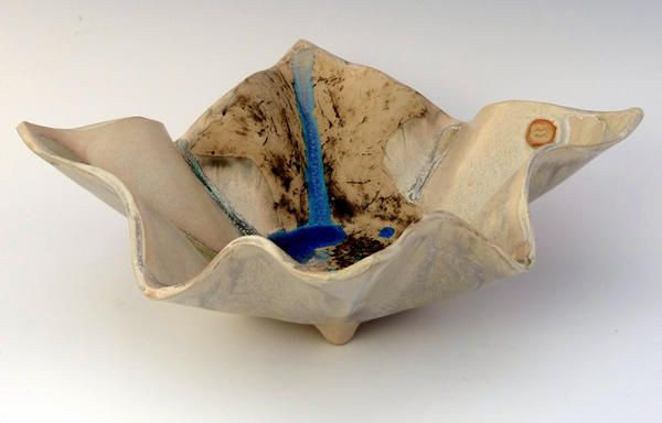 This piece is shaped with ripples to represent an aerial view of mountains and their valleys with rivers and lakes snaking through it. http://www.marketdirect.ie/ripple-landscape-dish