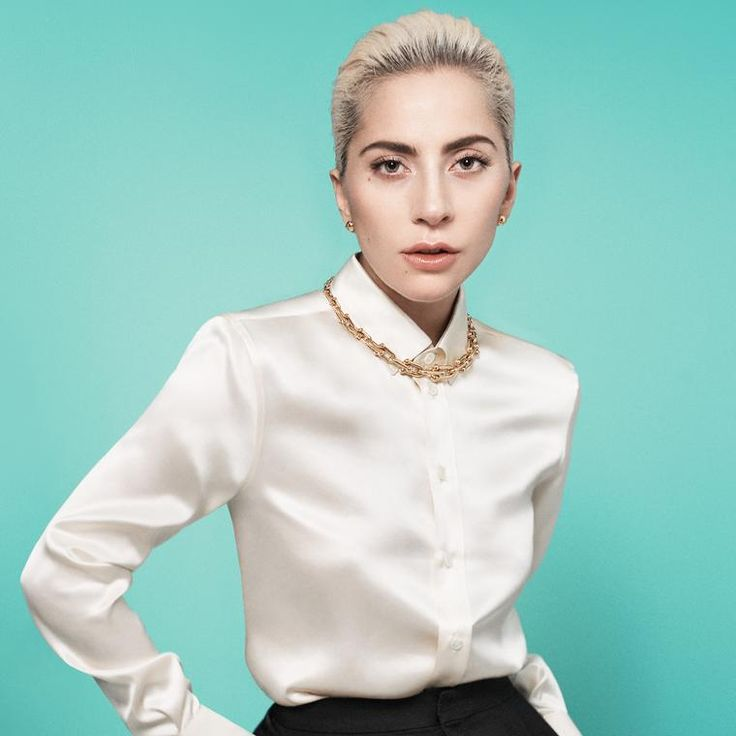 Lady Gaga for the Tiffany and Co. HardWear collection. Wearing gold chain necklace on a cream button up blouse, on Tiffany's classic blue. http://www.thejewelleryeditor.com/jewellery/article/tiffany-city-hardwear-gold-jewellery-collection-lady-gaga/ #jewelry