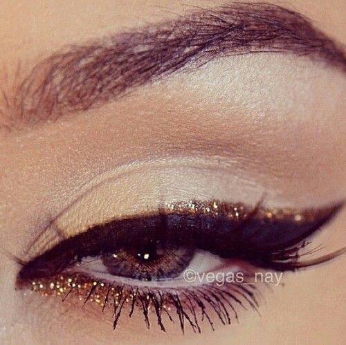Apply a satin neutral beige on eyelid with a lighter satin/shimmer highlighter shadow along brow bone and inner corner of eyes. Apply a sweep of back eyeliner on upper lid sweeping outward. Above the black eyeliner apply a sweep of glitter eyeliner and under eye starting from inner eye and sweeping glitter liner about halfway.