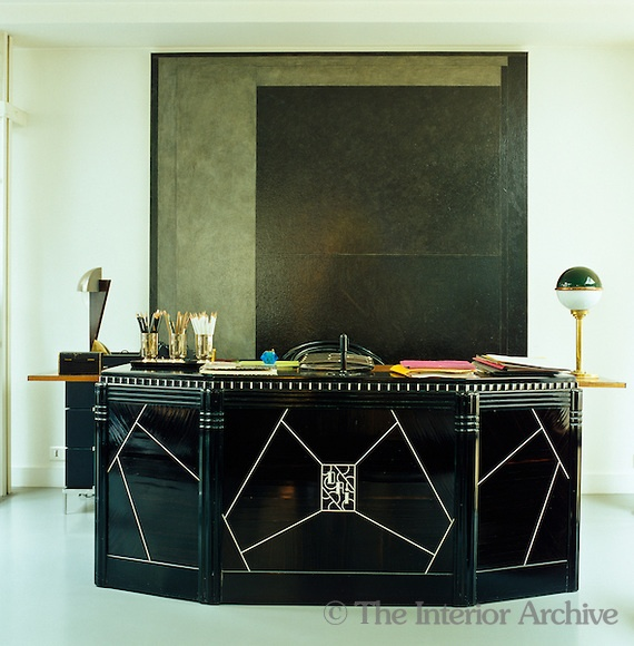 Andree Putman's Paris loft, converted in the 1970s - the large black-lacquer desk was designed by Jeanne Lanvin in the 1930s; its arrangement in front of a large  abstract painting in tones of grey and black cleverly implies a self-contained office space