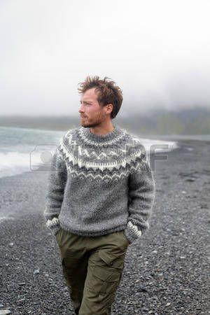 Man lopen op zwart zandstrand op IJsland dragen IJslandse trui. Knappe goed uitziende mannelijk model op zoek nadenkend op de oceaan zee. photo