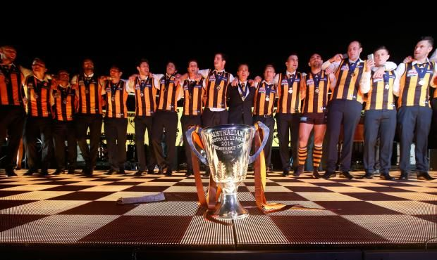 Hawks sing their club song around the cup to thousands of supporters after the 2014 Grand Final.