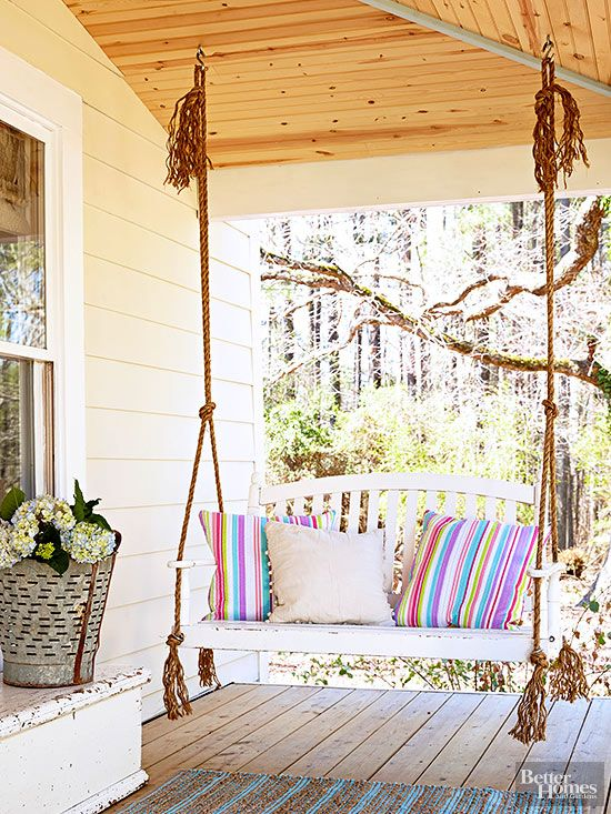 Reminiscent of an old farmhouse, this cozy porch takes it up a level with a charming porch swing, suspended from sturdy rope. Secret to Pretty:If country is your thing, keeping it simple with a few farmhouse or rustic touches, such as the metal bucket and the old-fashioned porch swing, strikes a clean, not cluttered, style.