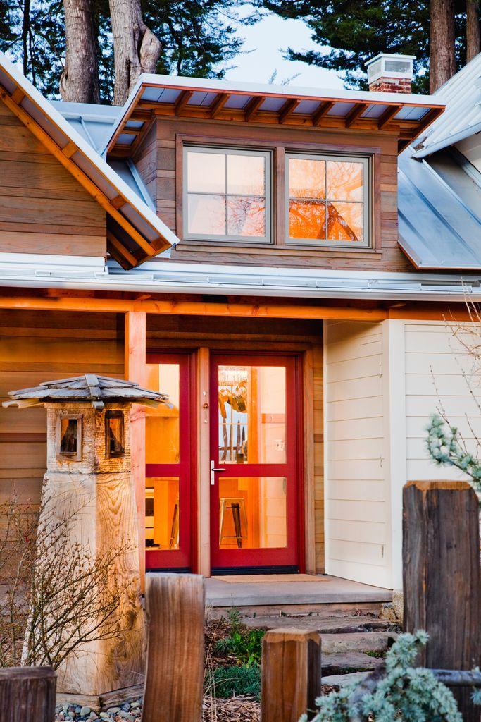 Вход в дом расположен между старой и новой его частями. В дом ведут красные остекленные двери. На крыше видна люкарна над кухней.  (архитектура,дизайн,экстерьер,интерьер,дизайн интерьера,мебель,энергосбережение,экология,теплоизоляция,утепление,викторианский,викториански дом,викторианский интерьер,викторианский стиль,термомодернизация,вход,прихожая,маленькая прихожая,идеи прихожей,оформление прихожей,мебель для прихожей,вешадка для прихожей,фасад) .