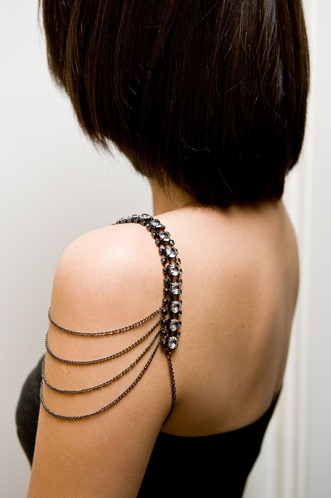 Rhinestone accented shoulder jewelry with draped chains.