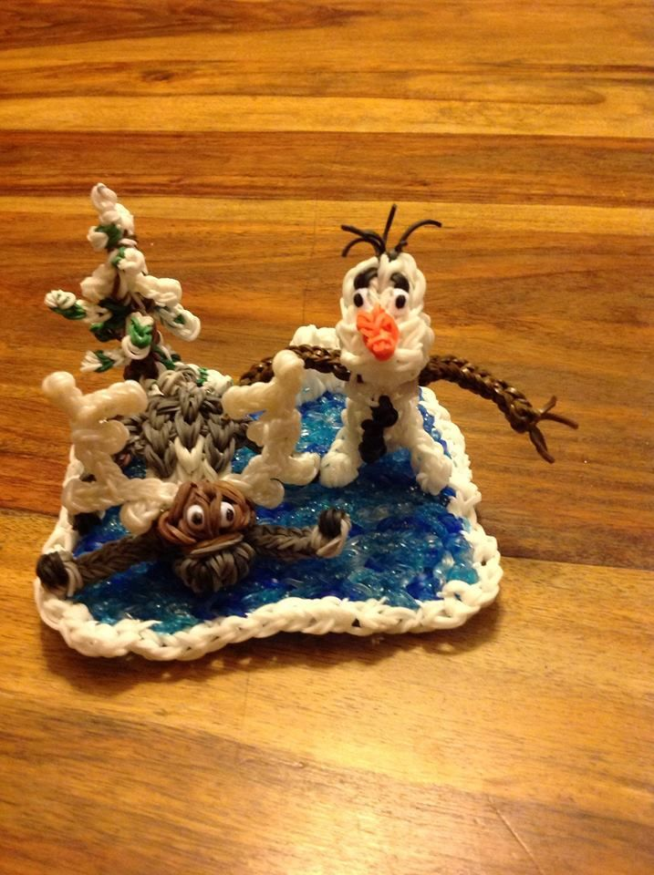 """FROZEN Scene. Designed/loomed by Coupon Cindy 04/08/14.  """"...made Sven from video by PG's Loomacy & Olaf by Bestchannel4kids. Made ice like Crystal makes murals using different blue jelly colors and clear. Snow on edges is a fishtail bracelet (double bands) -- sewed around the edge w bands. Put a few odd shaped snow pieces in back. Tree is a row of bands....branches made like arms in different sizes....some attached to loom as I loomed, some attached with slip knots after I took tree off…"""