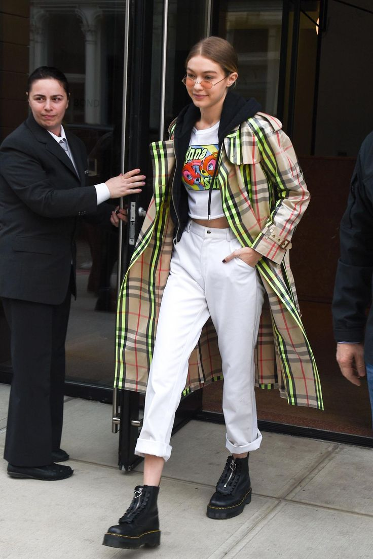 Gigi Hadid wearing Dr. Martens Lazy Oaf Jungle Boots, Burberry Laminated Check Trench Coat and Anna Sui Good Bunny Bad Bunny Tee