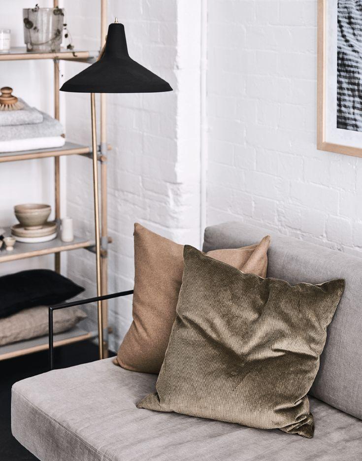 minimalist cushion styling on light grey sofa with black pendant light