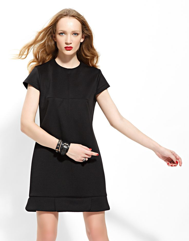 Black mini scuba dress with cap-sleeves, loose waist-line, petals finish on the bottom and back closure.