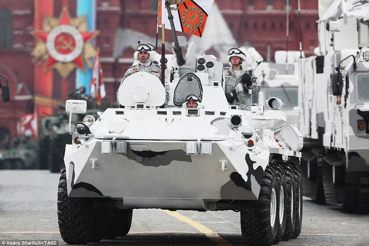A BTR-82A armoured personnel carrier rolls down Moscow's Red Square carrying military personnel dressed in white armu outfits