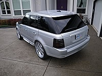 """2007 Range Rover Sport: Ghost lowering links, Tinted windows, E & G Grille, bumper and side vent inserts, Chrome door handles, custom black and aluminum Land Rover side badges, PIAA HID headlamps, Nokya gold fog lamp bulbs, LED; park, tail, reverse, and turn signal bulbs, Smoked tail lenses, Body Color matched; bottom cladding all around, bumper top pad, and wheels. 24"""" Giovanna multi piece look wheels, on Kumho 295/45 24 """" tires. AATAC"""