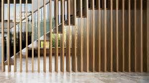 Dit kan ook! Een muur gemaakt van verticale lamellen van hout tegen een trap.