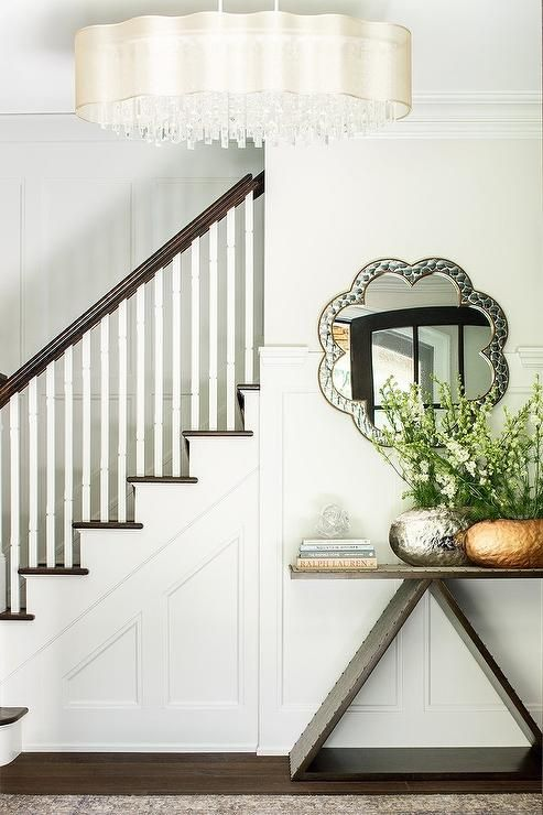 Chic Foyer Boasts A Wainscoted Staircase Wall Lined With A Wood And Linen Console  Table Topped With A Hammered Metal Gold Vase And A Hammered Silver Vase ...