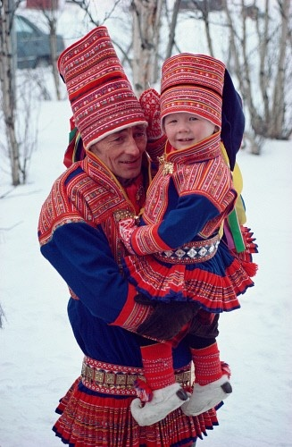 Sami costume: northern Sami man and child, with rows of metal-couched ribbon on their clothes and hats.
