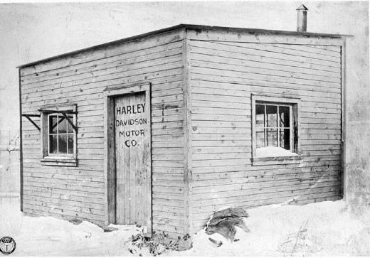 """William S. Harley and Arthur Davidson make available to the public the first production Harley-Davidson motorcycle. The factory in which they worked was a 10 x 15-foot wooden shed with the words """"Harley-Davidson Motor Company"""" crudely scrawled on the door.   Harley-Davidson 1903"""