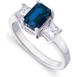 This very beautiful, quality blue sapphire gemstone with an emerald cut shape and bordered by two very good princess cut diamonds is a classic. When you mix good gemstones in a classic design, special things happen. This is one of those occasions.